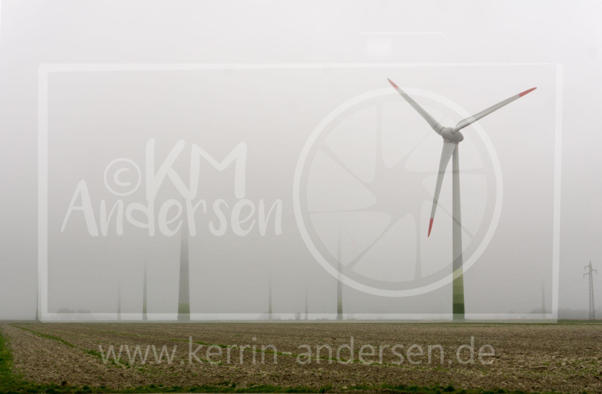 Der Nebel verschlinkt Windkrafträder in der Nähe des Eidersperwerks.